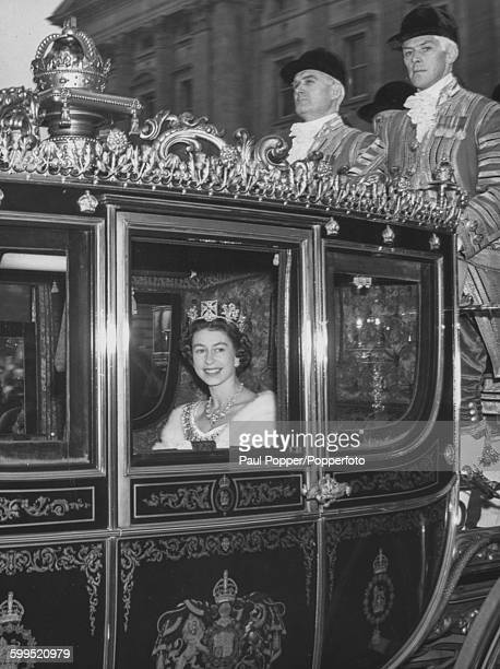 Queen Elizabeth II smiles as she rides in the Royal Irish State coach to the Palace of Westminster from Buckingham Palace for the State Opening of...