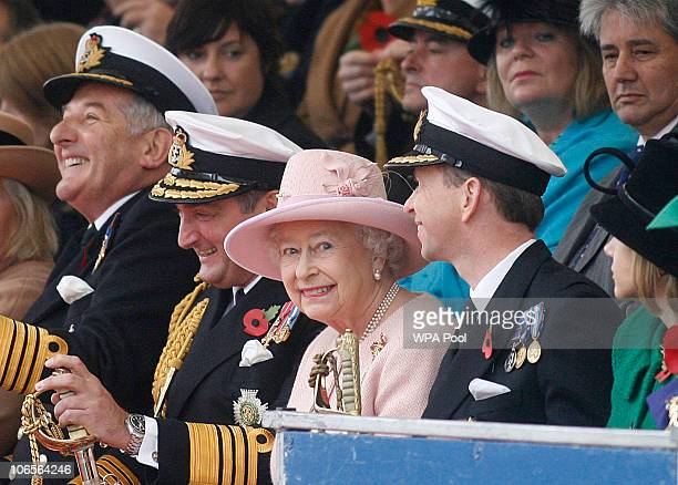 Queen Elizabeth II smiles as she sits with Captain Jerry Kyd Commanding officer of HMS Ark Royal and Sir Trevor Soar commanding officer Fleet on...