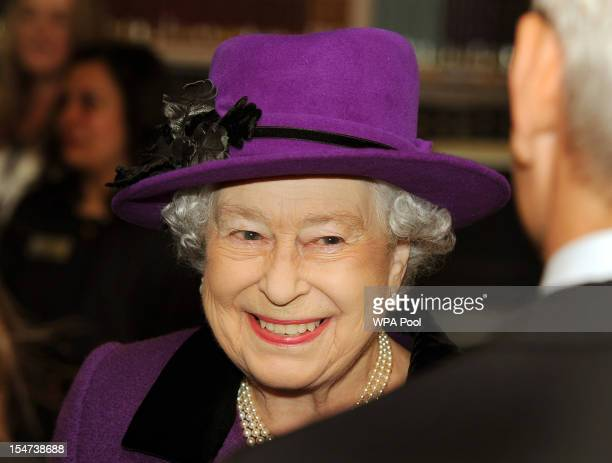 Queen Elizabeth II smiles as she talks to a member of staff during a visit to the British Film Institute on October 25, 2012 on the Southbank in...