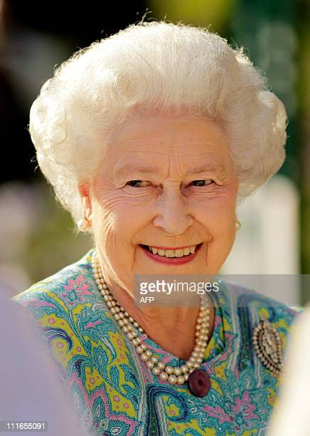 Queen Elizabeth II smiles as she talks to an exhibitor as she visits a garden at the Chelsea Flower Show in London, on May 24, 2010. The show, which...