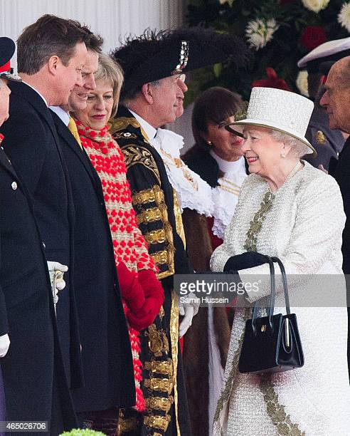 Queen Elizabeth II smiles as she talks to British Prime Minister David Cameron Liberal Democrats leader Nick Clegg and Home Secretary Theresa May as...