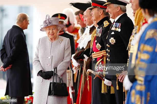 Queen Elizabeth II smiles as she waits with dignitaries for the arrival of the II Chinese President Xi Jinping at the official welcome ceremony at...