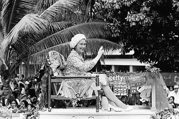 HM Queen Elizabeth II smiling and waving from a high seat on an official visit to Tuvalu circa 1982