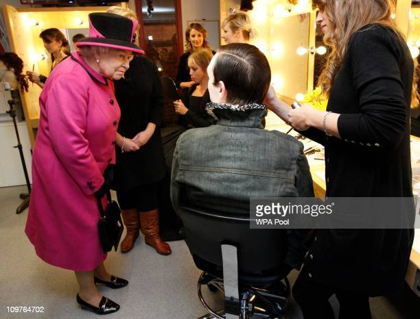 Queen Elizabeth II speaks to actors and makeup artists during her visit to the Royal Shakespeare Theatre on March 4 2011 in StratforduponAvon England