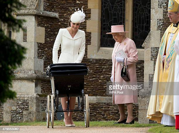 Queen Elizabeth II speaks to Catherine Duchess of Cambridge as she pushes in a pram Princess Charlotte of Cambridge at Church of St Mary Magdalene on...