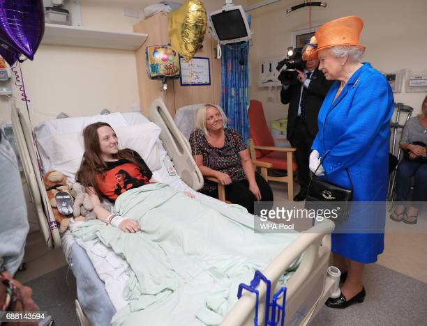 Queen Elizabeth II speaks to Millie Robson from Co Durham and her mother Marie during a visit to the Royal Manchester Children's Hospital to meet...