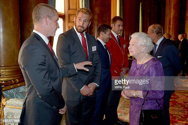 Queen Elizabeth II speaks with England Rugby Union head coach Stuart Lancaster and England captain Chris Robshaw at a reception at Buckingham Palace...