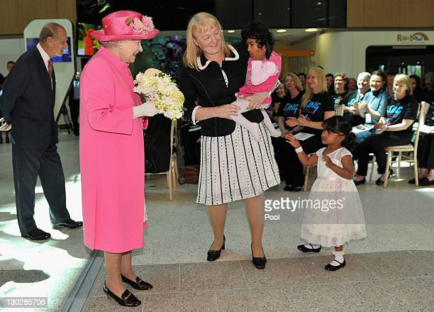 Queen Elizabeth II speaks with Moira Kelly as she holds previously conjoined twin Krishna as her twin sister Trishna looks on at the opening of the...