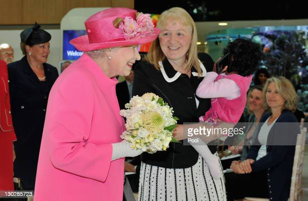 Queen Elizabeth II speaks with Moira Kelly as she holds previously conjoined twin Krishna at the opening of the new Royal Children's Hospital on...