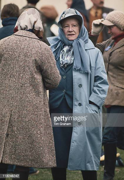 Queen Elizabeth II standing with her back to the camera talking to the Queen Mother at the Badminton Horse Trials in the grounds of Badminton House...