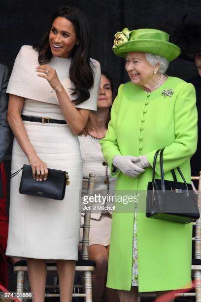 Queen Elizabeth II stands and laughs with Meghan Duchess of Sussex during a ceremony to open the new Mersey Gateway Bridge on June 14 2018 in the...