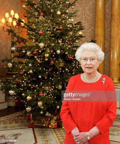 Queen Elizabeth II stands in front of a Christmas tree at Buckingham Palace after recording her Christmas Day television broadcast to the...