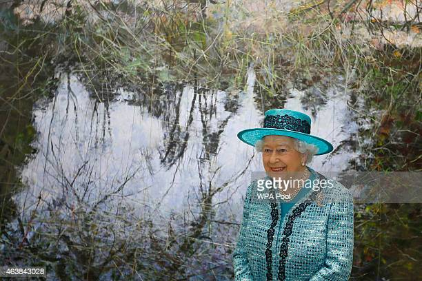Queen Elizabeth II stands in front of a painting by artist Gordon Smith during a visit to reopen Canada House on Trafalgar Square following an...