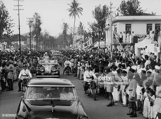Queen Elizabeth II stands in the back of an open top car and waves to crowds of residents as the royal motorcade makes its way through the streets of...