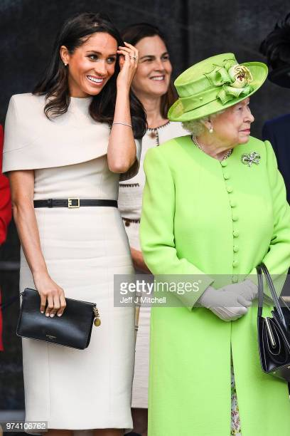 Queen Elizabeth II stands with Meghan Duchess of Sussex accompanied by Samantha Cohen during a ceremony to open the new Mersey Gateway Bridge on June...