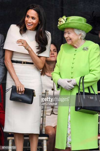 Queen Elizabeth II stands with Meghan Duchess of Sussex during a ceremony to open the new Mersey Gateway Bridge on June 14 2018 in the town of Widnes...