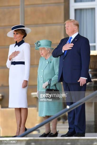 Queen Elizabeth II stands with US President Donald Trump and US First Lady Melania Trump as they listen to the US national anthem during a welcome...