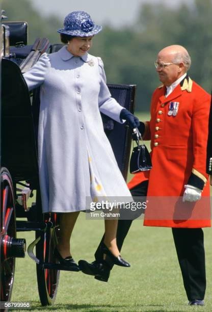 Queen Elizabeth II steps out of a carriage as she arrives at Guards Polo Club, Smith's Lawn.