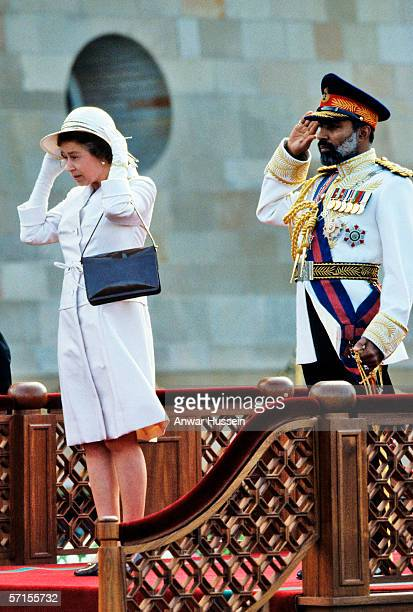 Queen Elizabeth II struggles with her hat in the wind whilst protocol demands that Sultan Qaboos stands rigidly to attention during the Queen's visit...