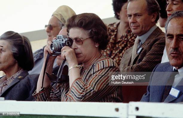 Queen Elizabeth II takes a photograph whilst watching the 1982 Windsor Horse Show.