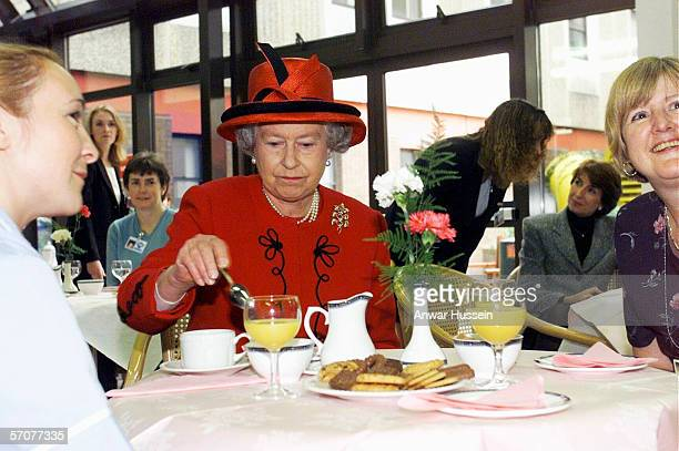 Queen Elizabeth II takes a tea break with hospital staff during her visit to Manchester Royal Infirmary on October 15 1999