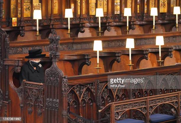 Queen Elizabeth II takes her seat during the funeral of Prince Philip, Duke of Edinburgh in St George's Chapel at Windsor Castle on April 17, 2021 in...