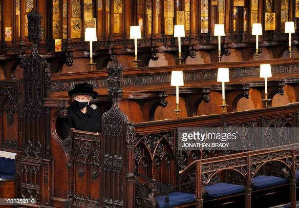 Queen Elizabeth II takes her seat for the funeral service of Britain's Prince Philip, Duke of Edinburgh inside St George's Chapel in Windsor Castle...