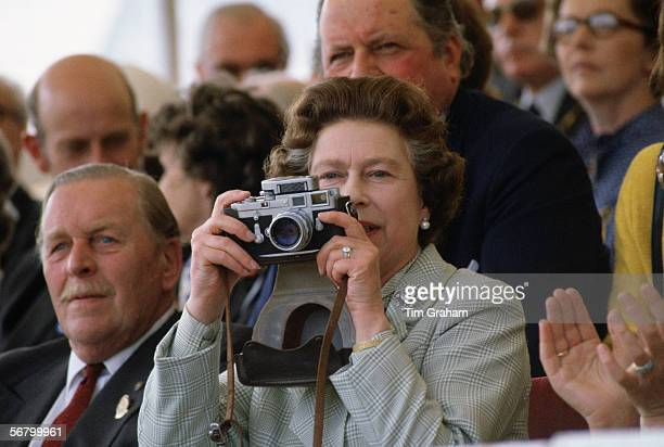 Queen Elizabeth II taking a picture with her camera at the Royal Windsor Horse Show