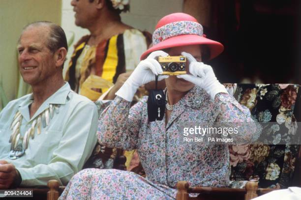 Queen Elizabeth II taking photographs during her visit to the South Sea Islands of Tuvalu Behind her is the Duke of Edinburgh