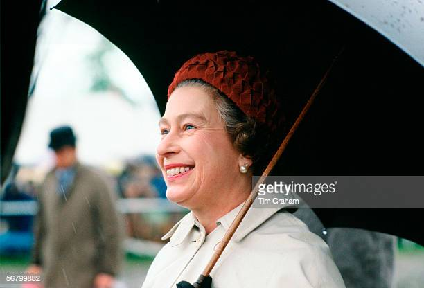 Queen Elizabeth II taking shelter under an umbrella whilst presenting prizes at the Royal Windsor Horse Show