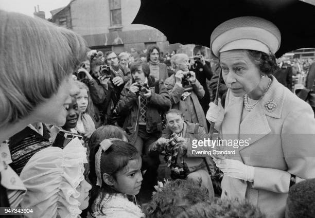 Queen Elizabeth II talking to children in Deptford during a walkabout to commemorate her Silver Jubilee London UK 9th June 1977