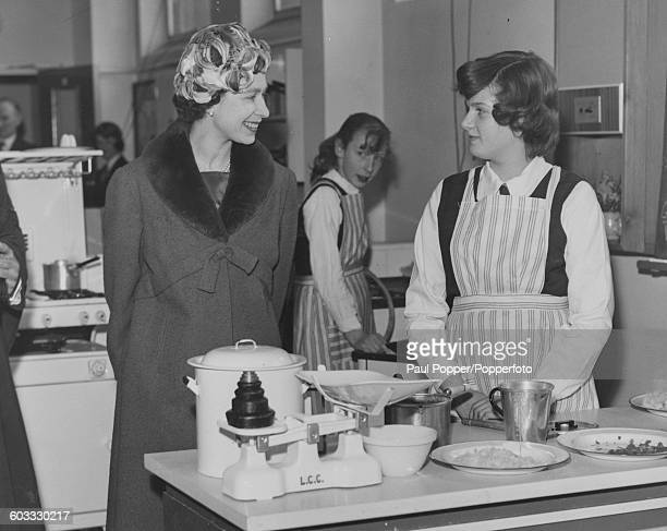 Queen Elizabeth II talks to 13 year old Carol Hummesston in the cooking classroom during a visit to St Michael's School in Westminster London on...