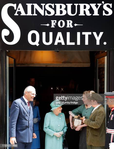 Queen Elizabeth II talks to actors in period costume as she visits a replica of one of the original Sainsbury's stores in Covent Garden to mark the...