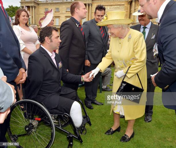 Queen Elizabeth II talks to Andy Reid ex 3rd Battlion the Yorkshire Regiment who lost both legs and an arm in Afghanistan in 2009 in a bomb attack as...