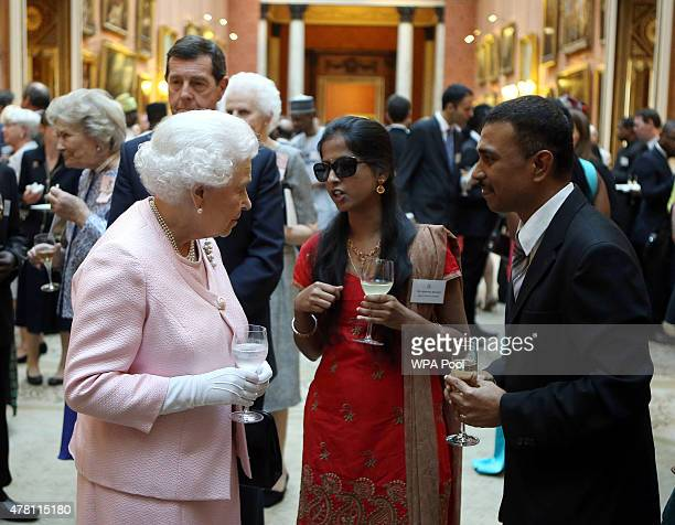 Queen Elizabeth II talks to guests at a reception at Buckingham Palace to celebrate The Queen's Young Leaders programme and present awards to the...