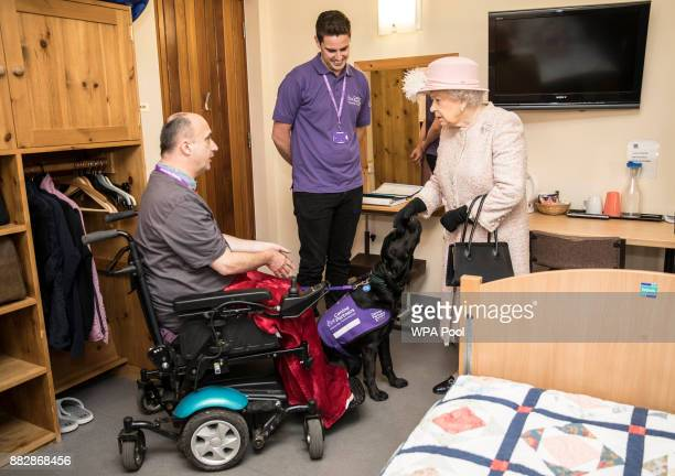 Queen Elizabeth II talks to Jonathan Fletcher and his help dog 'Georgia' in a lodging room at the headquarters of the charity 'Canine Partners' on...