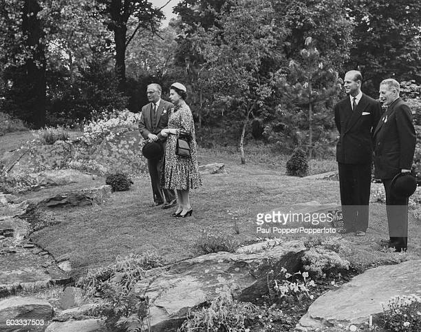 Queen Elizabeth II talks with an unknown man as the Duke of Edinburgh talks to the Hon David BowesLyon during a viewing of a rock garden at the...