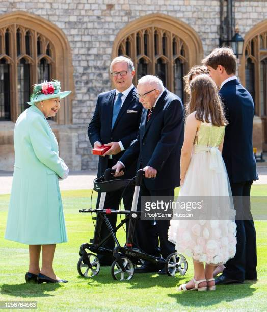 Queen Elizabeth II talks with Captain Sir Thomas Moore and his family after presenting him with the insignia of Knight Bachelor during an investiture...