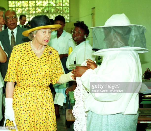 Queen Elizabeth II talks with one of the seamstresses in the garment production workshop of the Laws Street Training Centre during a visit to...