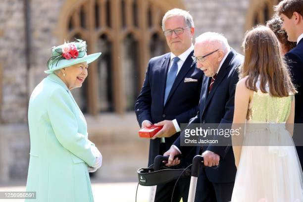 Queen Elizabeth II talks with the family of Captain Sir Thomas Moore after awarding him with the insignia of Knight Bachelor at Windsor Castle on...