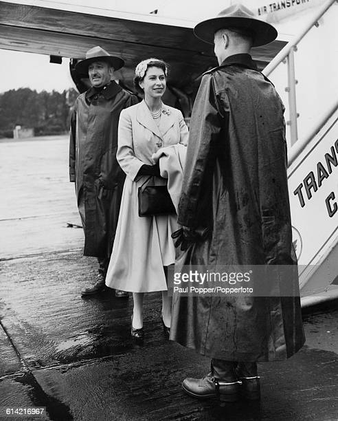 Queen Elizabeth II talks with two members of the Canadian mounted police at Tangmere aerodrome in Sussex as she sees Prince Philip Duke of Edinburgh...