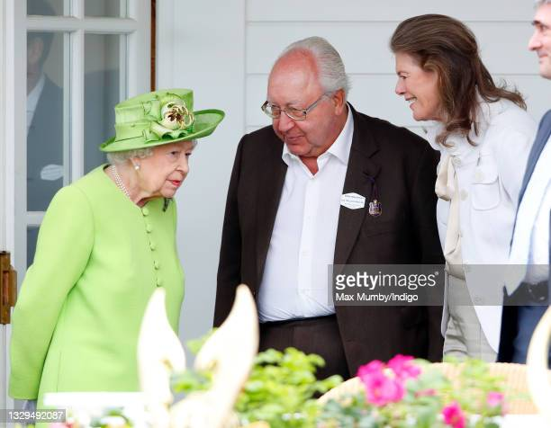 Queen Elizabeth II talks with Urs Schwarzenbach and Francesca Schwarzenbach as she attends the Out-Sourcing Inc. Royal Windsor Cup polo match and a...