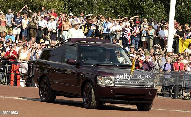 Queen Elizabeth II, The Queen, and Prince Edward, Duke of Edinburgh, stand in a landrover and acknowledge the crowds on National Commemoration Day...