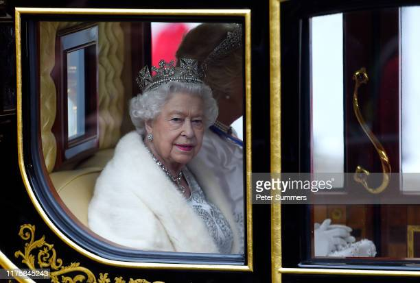Queen Elizabeth II travels by carriage along The Mall ahead of the State Opening of Parliament at the Palace of Westminster on October 14 2019 in...