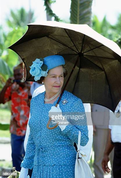 Queen Elizabeth II under a sun umbrella during a visit to Tuvalu in the South Pacific