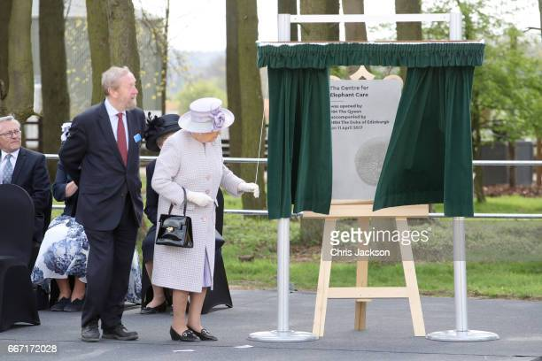 Queen Elizabeth II unveils a plaque to mark the formal opening of the Elephant Centre as she and Prince Philip Duke of Edinburgh visit the Elephant...