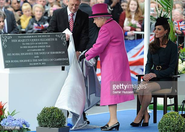 Queen Elizabeth II unveils a plaque with Leicester City mayor Sir Peter Soulby during her visit to Leicester on March 8 2012 in Leicester England The...