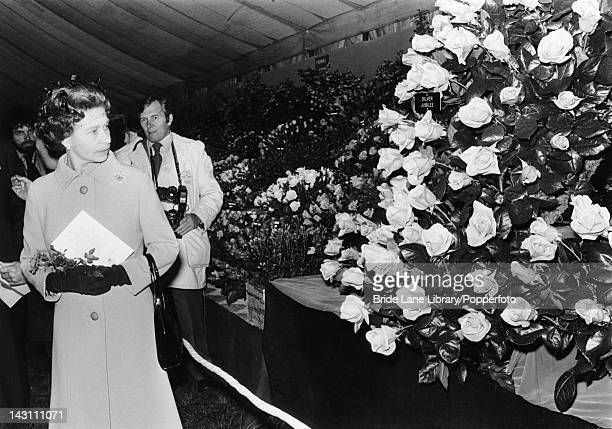Queen Elizabeth II viewing a display of tea roses named 'Silver Jubilee' to mark her jubilee year during a visit to the Chelsea Flower Show London...