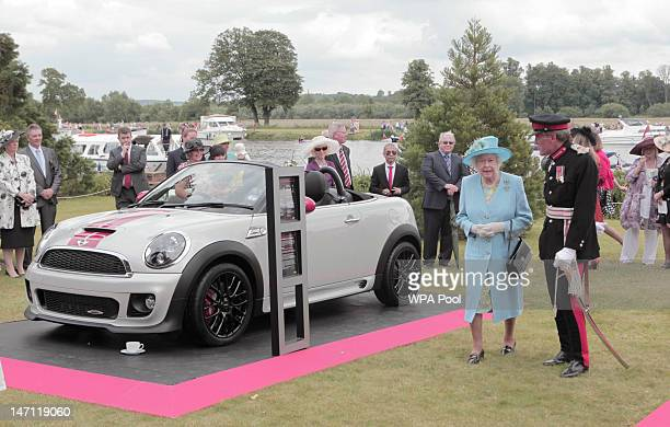 Queen Elizabeth II views a Mini during the Three Counties Diamond Jubilee River Pageant at the Henley Business College on June 25 2012 in Henley on...
