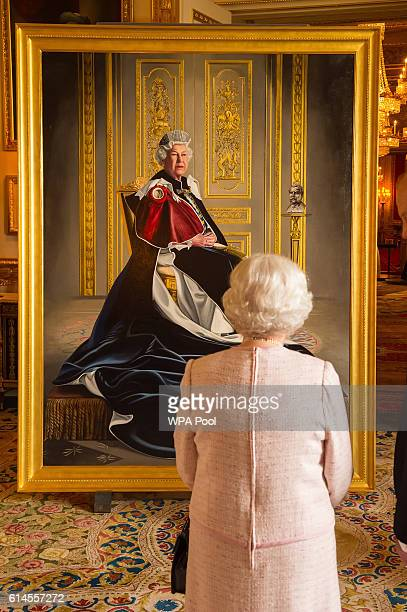 Queen Elizabeth II views a portrait of herself by British artist Henry Ward marking six decades of patronage to the British Red Cross which has been...